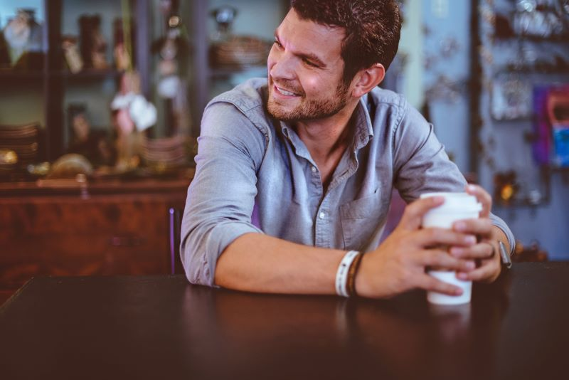 smiling man with cup of coffee